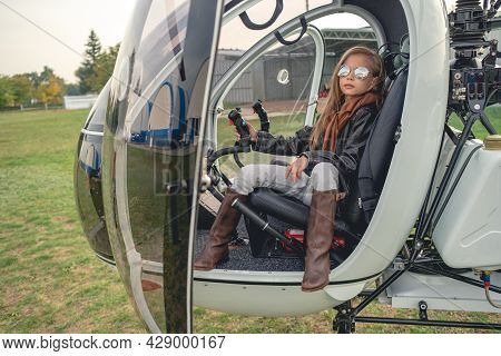 Confident Tween Girl In Mirrored Sunglasses Sitting In Helicopter