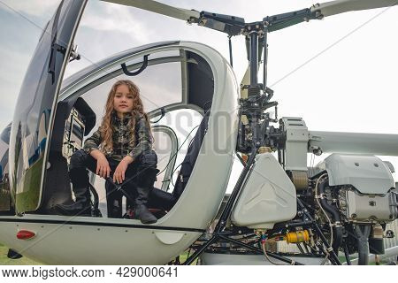 Tween Girl In Camouflage Style Tunic Sitting In Open Helicopter Cockpit
