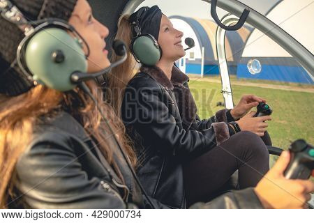 Smiling Preteen Girls In Headsets Looking Up At Sky In Helicopter Cockpit