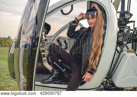 Confident Tween Girl Sitting In Open Cockpit Of Helicopter