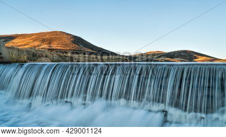 water cascading over a diversion dam at creek in Colorado foothills, sunrise springtime scenery
