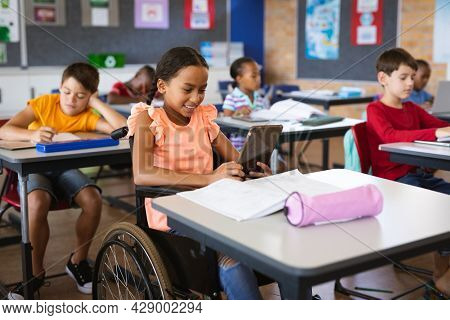 Disabled african american girl using digital tablet while sitting on wheelchair at elementary school. school and education concept