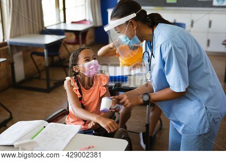 Female health worker wearing face shield measuring temperature of disabled girl at elementary school. education back to school health safety during covid19 coronavirus pandemic.