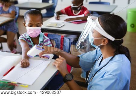 Female health worker wearing face shield measuring temperature of a girl at elementary school. education back to school health safety during covid19 coronavirus pandemic.