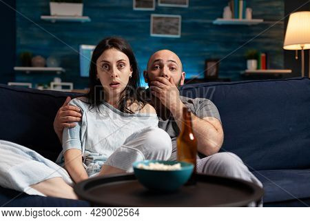 Amazed Confused Couple Watching Movie On Tv At Night And Eating Popcorn, Drinking Beer Having Facial