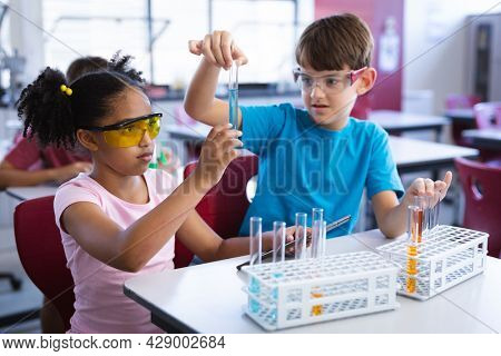African american girl and caucasian boy holding test tube in science class at elementary school. school and education concept
