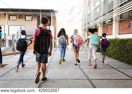 Rear view of group of diverse students with backpacks running at elementary school. education back to school health safety during covid19 coronavirus pandemic.