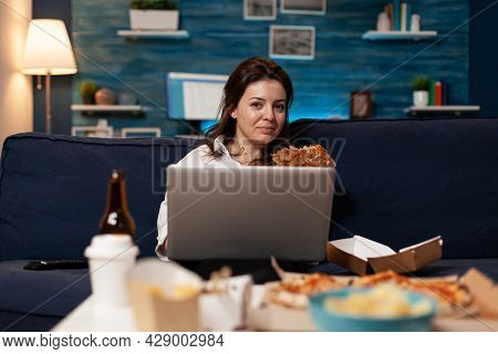 Caucasian Female Sitting On Sofa Eating Tasty Delicious Burger While Working On Laptop Computer In L