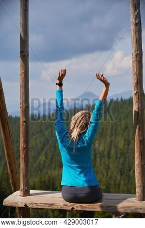 Rear View Of Girl Sitting On Seat Of Large Wooden Swing With Straight Back And Outstretched Arms, Lo