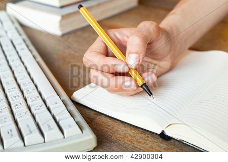 Young woman hand writes a pen in a notebook, computer keyboard and a stack of books in background