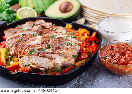Chicken Fajitas With Bell Pepper And Onion In A Pan, Served With Salsa Asada, Sour Cream, Avocado An