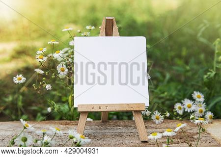 Easel On Lawn. Artistic Equipment On Nature. Empty Artist Canvas On Wood Easel. Summer Natur Backgro
