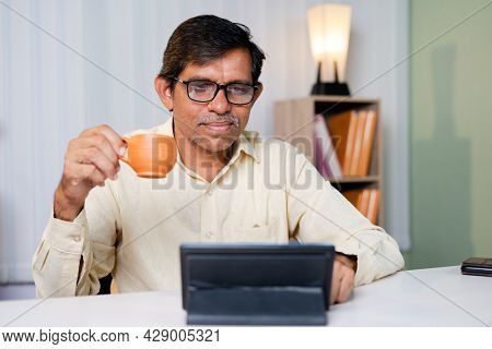 Businessman Having Coffee While Using Or Reading News, Social Media And Internet On Digital Tablet A