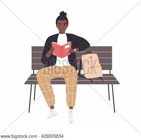 Student Studying And Reading Book Outdoors. African American Man Sitting On Bench With Literature In