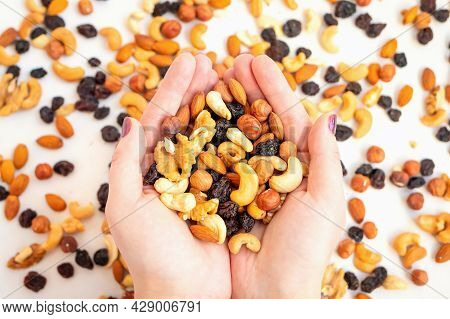 Close Up Of Woman's Hand With Nuts And Raisins On Background Of Scattered Pile Of Nuts On White Back