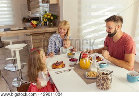 Young Parents Having Breakfast With Their Children At Home, Mother Holding Baby Boy In Her Lap And F