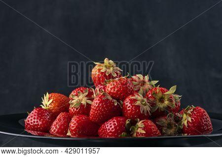 Ripe Sweet Strawberries On Black Background. Fresh Summer Berries, Close Up. Seasonal Berries On A P