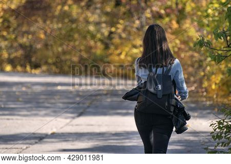 Brunette Woman Walks Along The Alley Of An Autumn Park. Lonely Girl In The Sunny Forest. Back View