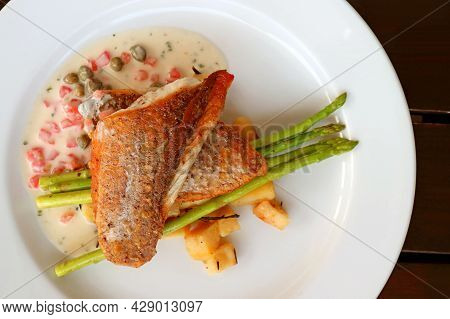 Top View Of Pan Seared Sea Bass With Tomato Caper Mustard Cream Sauce On White Plate