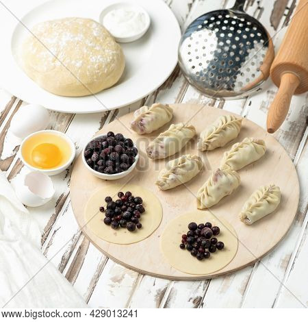 Cooking Sweet Dumplings. Blackcurrant Filling On Rolling Raw Dough At Wooden Cutting Board. Ingredie