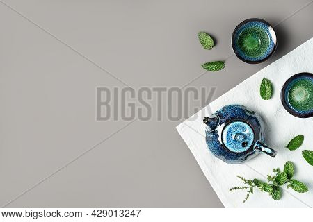 Green Tea In A Dark Blue Clay Teapot And Small Cups On Dark Grey And Pastel Blue Background With Min