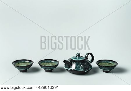 Green Tea In A Dark Turquoise Clay Teapot And Small Cups Lined On Pastel Background. Creative Minima