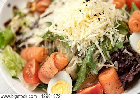 Caesar Salad With Red Fish, Herbs And Grated Cheese. Close-up Shot. Horizontal Format. Soft Focus.