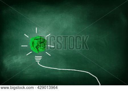 Business Idea Concept : Green Crumpled Paper Ball Light Bulb Lighting Grow Around On Chalkboard.