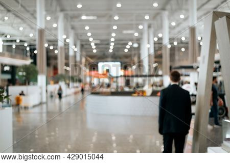 Defocused Shopping Mall Background, Large Illuminated Hall, Security Guard Rear View. Blurred Backdr
