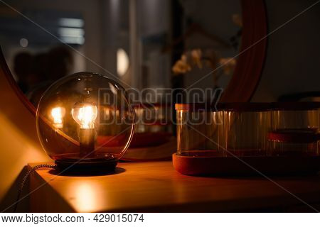 Home Evening Interior Close Up. Luminous Light Bulb Inside Glass Ball, Standing On Wooden Chest Of D