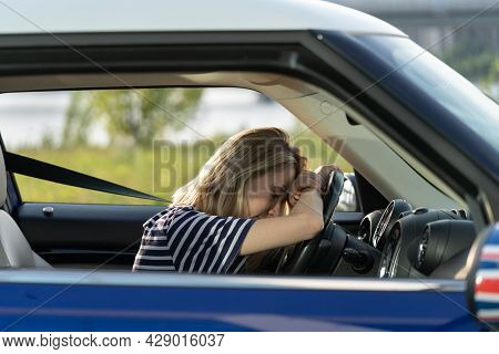 Tired Exhausted Woman Of Middle Age Lying On Steering Wheel In Car Driving. Unhappy Depressed Sleepy