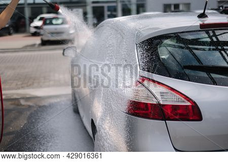 Back View Of Young Woman Cleaning Her Car On Self Service Car. Female Washing With Jet Sprayer. Whit