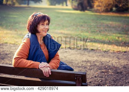 Middle Aged Caucasian Woman Sits Alone At Golden Autumn Park. Mature Woman Relaxing In Autumn Landsc