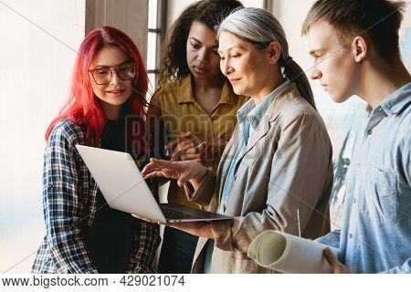 Mature teacher using laptop while talking with her students during class in art school indoors