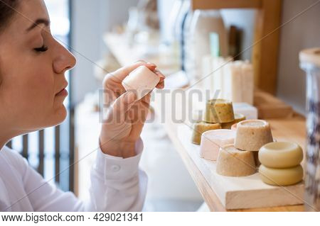 Woman Sniffing Organic Soap While Choosing At Eco Friendly Store.