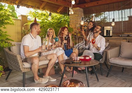 Group Of Cheerful Young People Having Fun Celebrating Friend's Birthday, Drinking Cocktails, Singing
