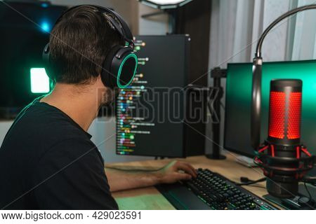 Back view of a young man gamer streamer in headphones playing on computer talking with players on chat in gaming competition