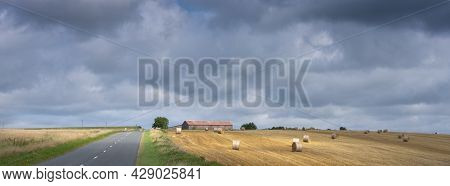Cloudy Sky And Summer Countryside Landscape With Straw Bales And Barn In French Ardennes Near Charle
