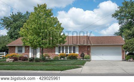 Brick Ranch House with Yellow Daisy Garden