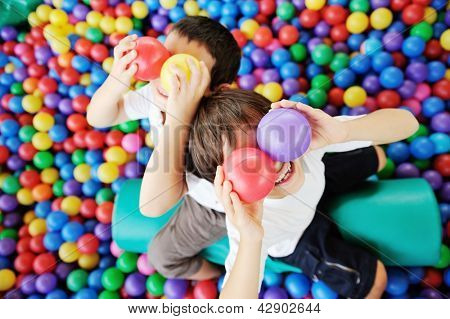 Happy children playing and having fun at kindergarten with colorful balls on eyes