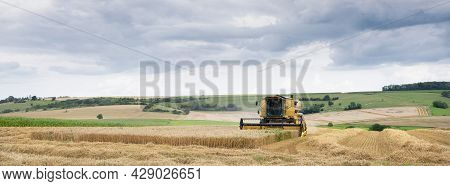 Rural Landscape Of Northern France With Combine During Harvest In French Countryside Landscape Near