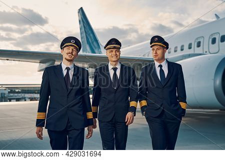Three Stylish Handsome Pilots Walking Across The Airdrome