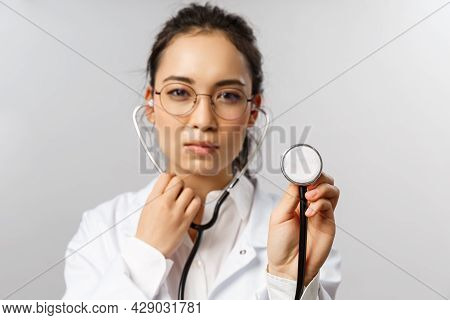Covid19, Coronavirus, Healthcare And Doctors Concept. Portrait Of Serious-looking Female Doctor Duri