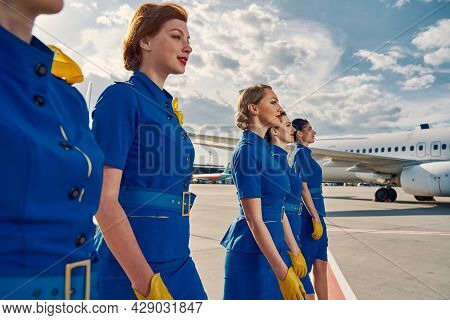Group Of Pretty Air Hostesses Crossing The Airfield