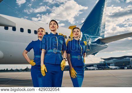 Slim Flight Attendants By A Landed Jetliner
