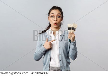 Creativity, Repairs And Overhaul Concept. Amused And Curious Asian Girl In Glasses, Holding Brushes