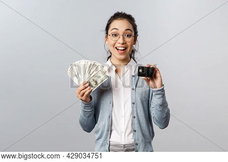 Business, Finance And Investment Concept. Amused Happy Asian Girl Decides Save For Her Vacation, Pla