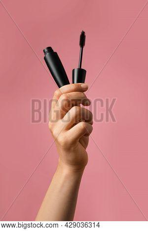 Woman Holding Mascara For Eyelashes On Dusty Rose Background, Closeup