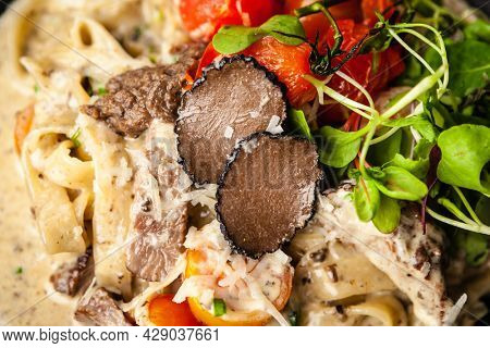 Black Angus beef tagliatelle pasta with fresh black truffles and parmegano. Delicious healthy traditional food closeup served for lunch in modern gourmet cuisine restaurant