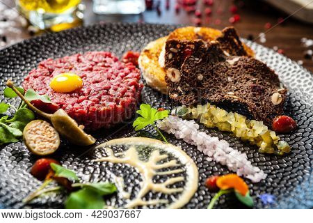 Beef tartare from Black Angus. Onion, quail egg, tomato sauce, mustard mayonnaise. Delicious healthy Italian traditional food closeup served for lunch in modern gourmet cuisine restaurant